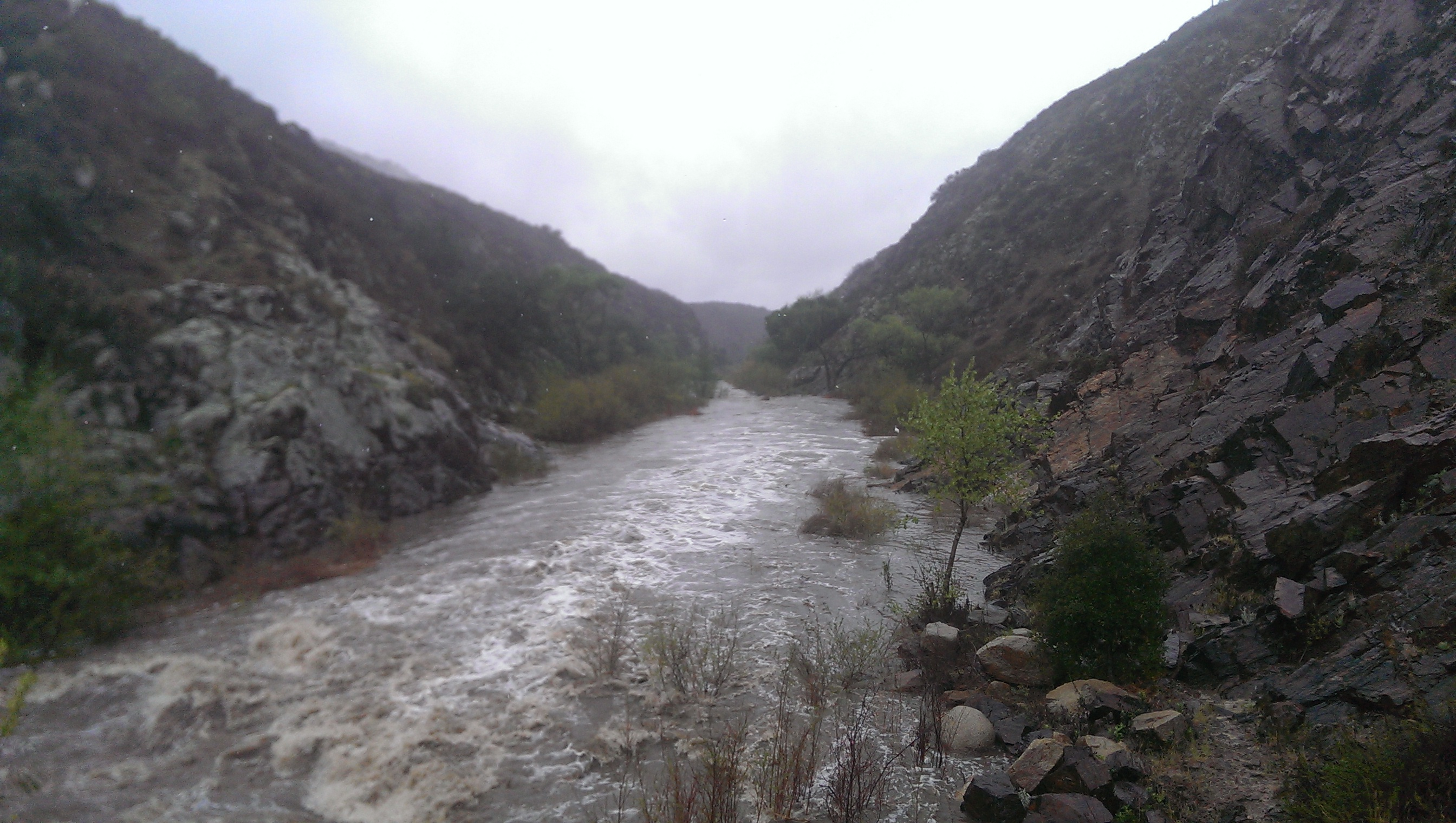 River in canyon flowing at high volume, vanishing into distance