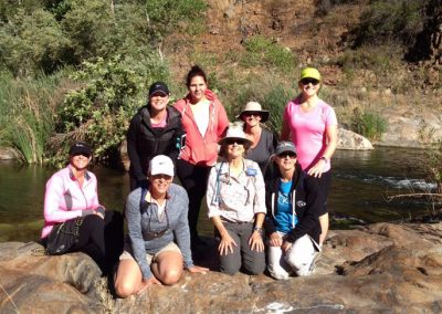 group of hikers posing for photo near river