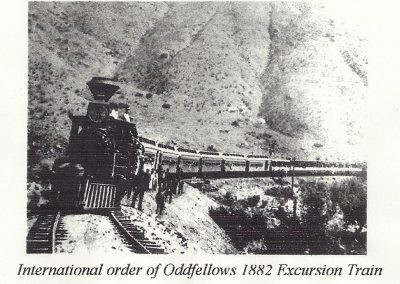 Locomotive on train tracks with people standing outside