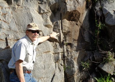 adult male pointing to rock formation