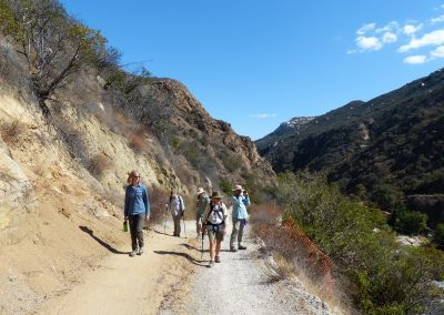 5 hikers climbing up a dirt road hear river
