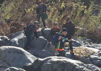 5 young hikers climbing on rocks