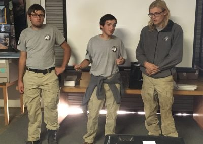 3 young people stand in front of a projector in a classroom