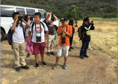 van load of students with binoculars getting ready to hike