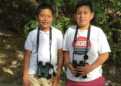 2 young students with binoculars smiling