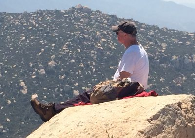 hiker sits on top of a rock looking outward. A rocky hill is in the background