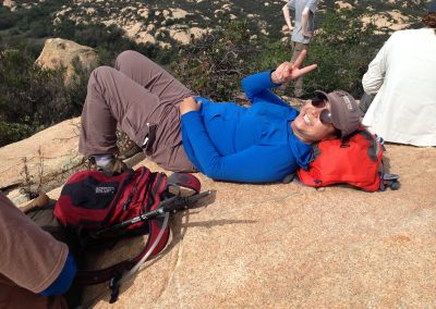 hiker resting on back giving peace sign with fingers