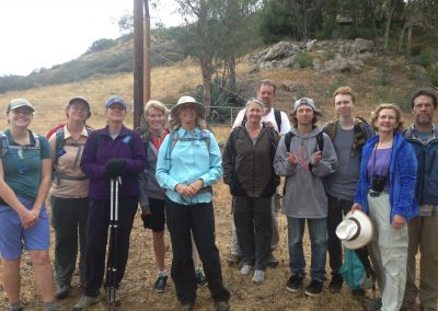 11 hikers stand in a row with wooden posts and a hill in the back ground