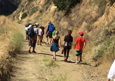 8 young students hike down a trail following 1 adult