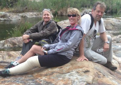 3 hikers sitting on a rock near the river