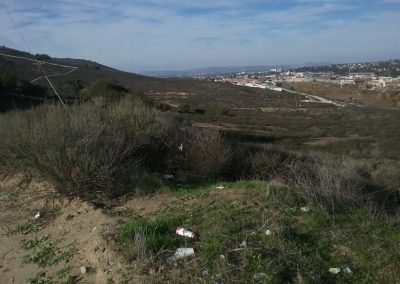 Housing development in background at base of slope, trash in forground