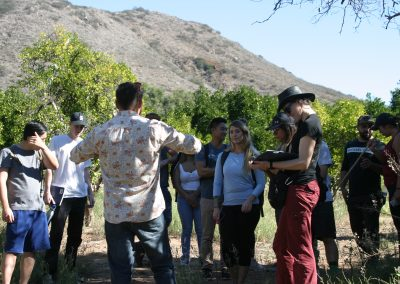 A man speaks to a group of students, fruit trees and hills in the background