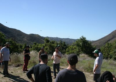 A man speaks to a circle of students, fruit trees behind him