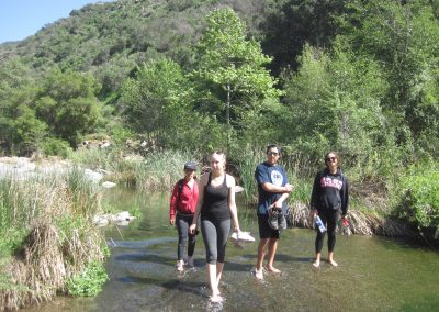 Four barefoot students crossing the river