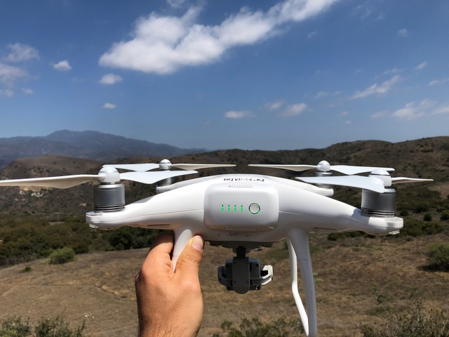 a hand holding a white drone, landscape in background