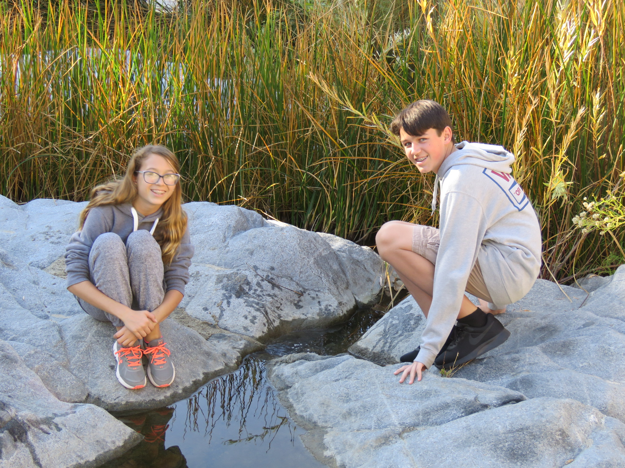 two young people kneeling on rocks near water