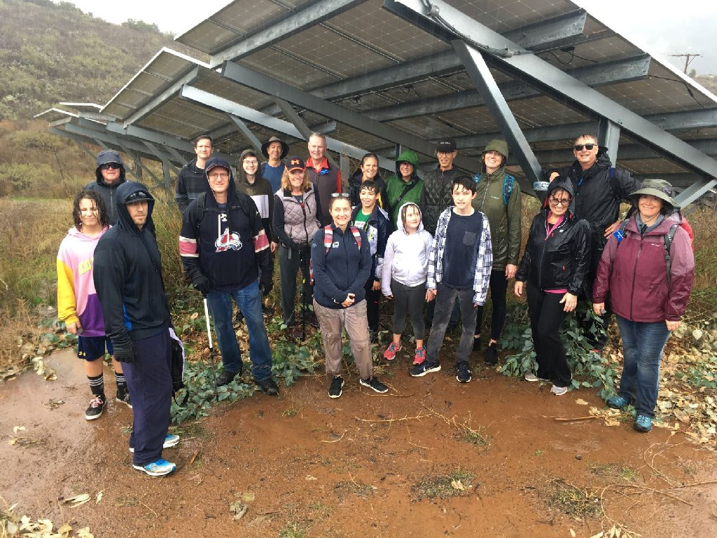 group of 20 hikers under a solar panel in the raiin