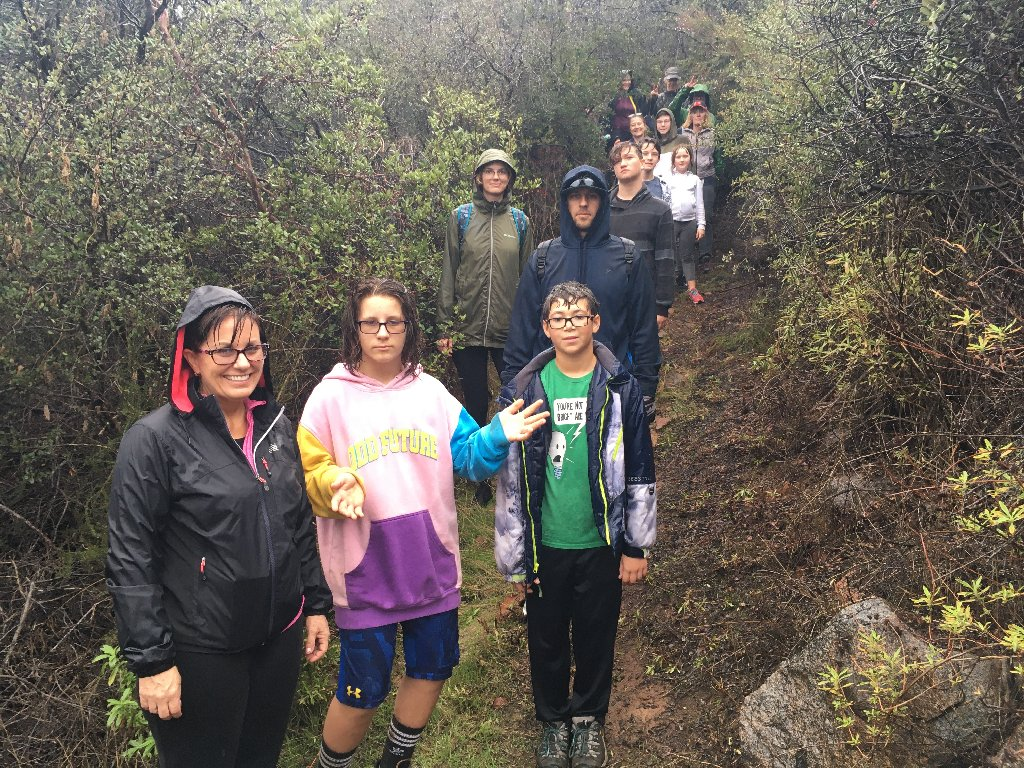 13 people standing on a trail in the rain