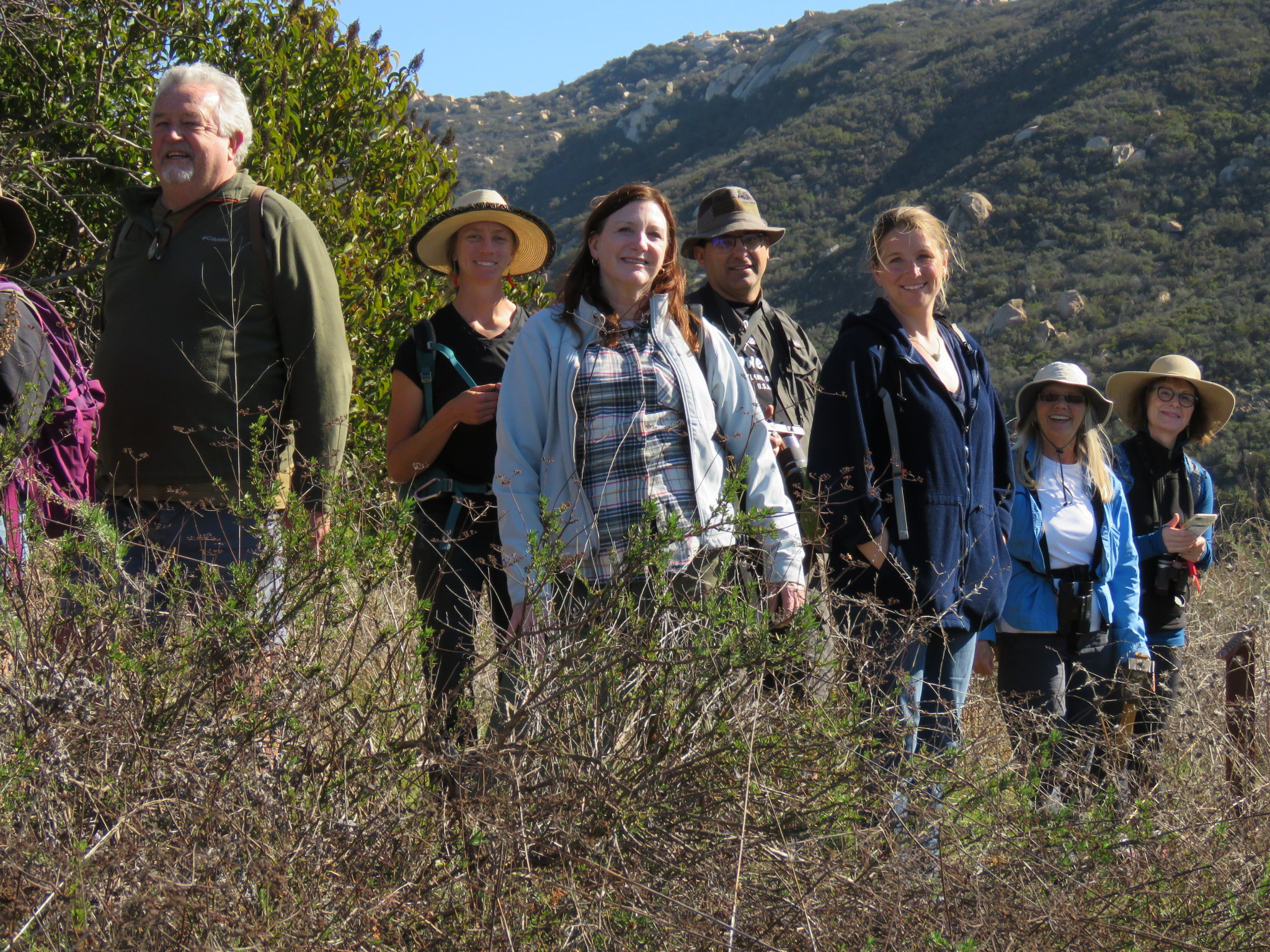 8 hikers stand smiling in chaparral background