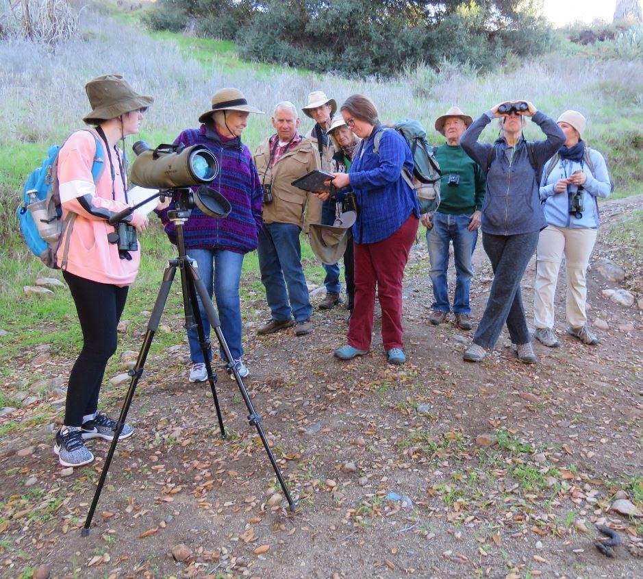 10 people standing looking through binoculars