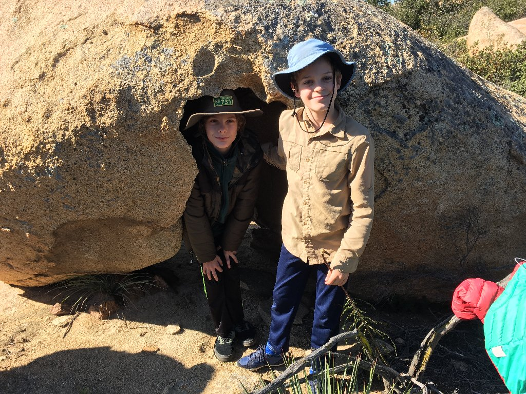 two young boys in front of a rock