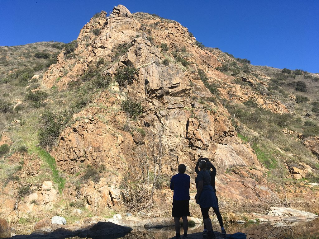 two people silhouetted in front of a sunny rock cliff